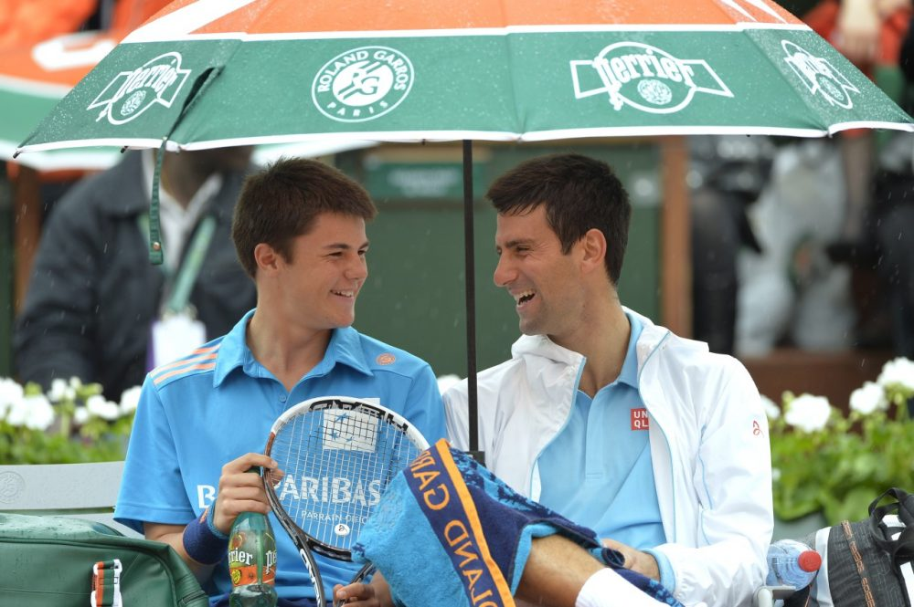 Novak Djokovic (right) shares a laugh with a ball boy during his French Open first round match. (Miguel Medina/AFP/Getty Images)