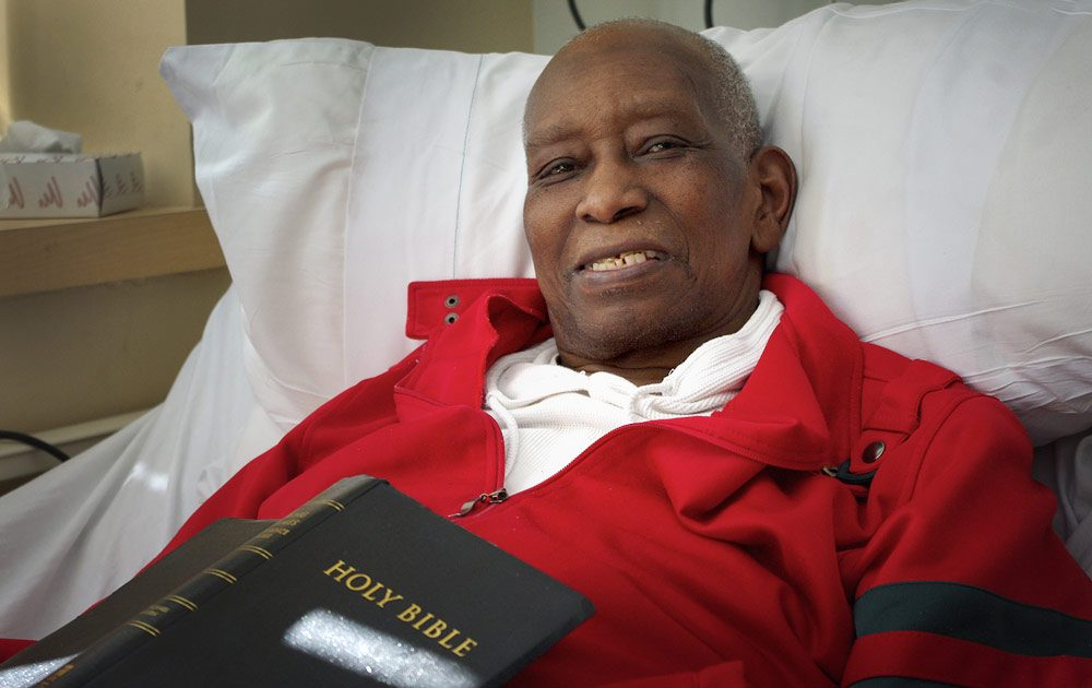 """Kervin Elleyne, 67, receives end-of-life care at the Barbara McInnis House in Boston, which has 100 beds for homeless and undocumented individuals. He says it's """"one of the best places that a person could ever be."""" (Gabrielle Emanuel/WBUR)"""