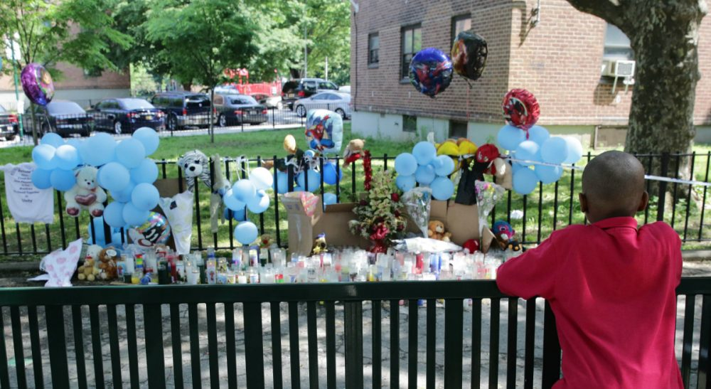 A boy looks at a memorial outside the Boulevard Houses after a news conference there in the borough of Brooklyn in New York on Wednesday, June 4, 2014. On Sunday, June, 1, two children were stabbed at at the housing complex. (Peter Morgan/AP)