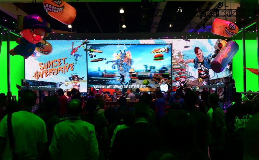 A crowd gathers around a big screen as gamers play Sunset Overdrive on Xbox at annual E3 video game extravaganza in Los Angeles, California on June 10, 2014. (Frederic J. Brown/AFP/Getty Images)