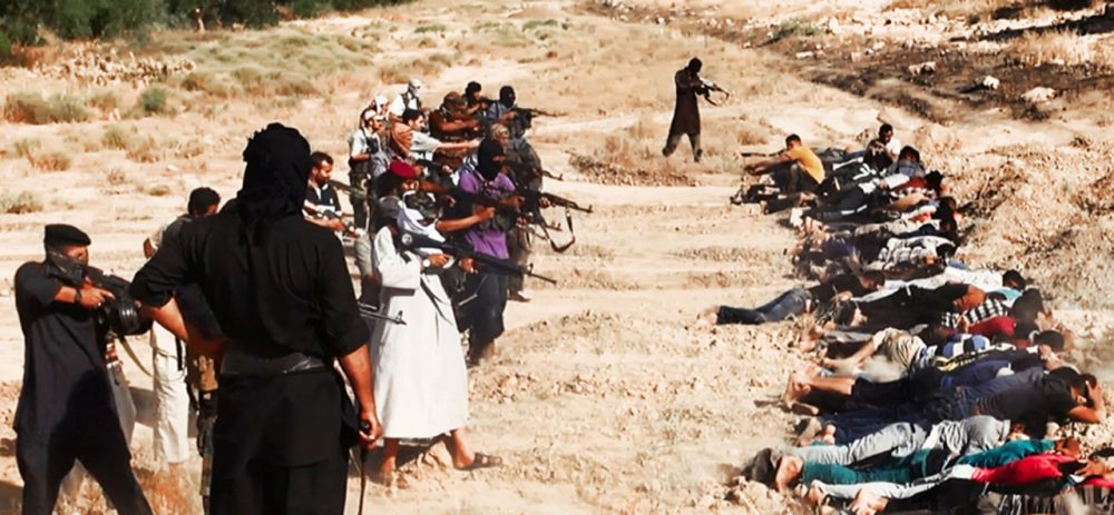 This image posted on a militant website on Saturday, June 14, 2014, which has been verified and is consistent with other AP reporting, appears to show militants from the al-Qaida-inspired Islamic State in Iraq and Syria (ISIS) taking aim at captured Iraqi soldiers wearing plain clothes after taking over a base in Tikrit, Iraq. (AP Photo via militant website)