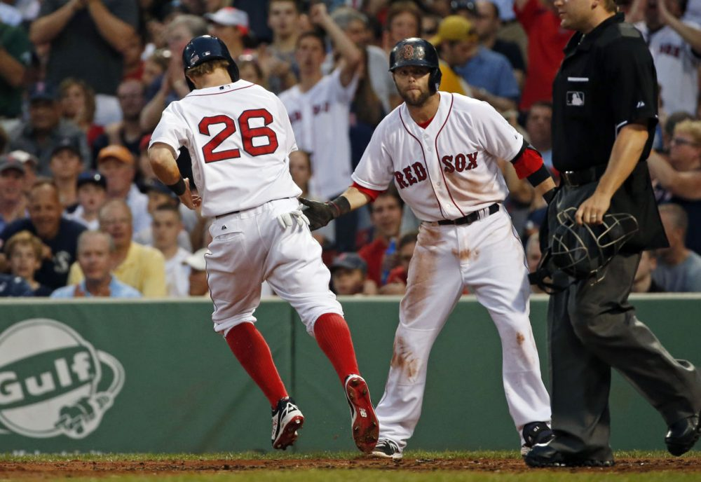Red Sox's Brock Holt (26) is congratulated by teammate Dustin Pedroia as he scores on a sacrifice fly by Xander Bogaerts in the third inning. (AP/Elise Amendola)