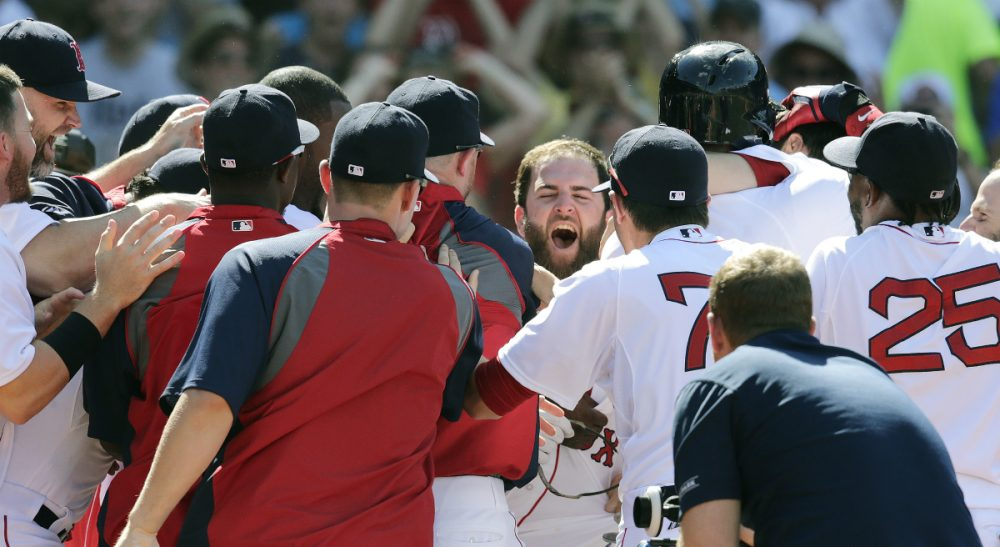 Boston Red Sox's Mike Napoli, center, smiles as he is congratulated by teammates after hitting the game-winning, walk-off home run against the Minnesota Twins in the 10th inning of a baseball game at Fenway Park in Boston, Wednesday, June 18, 2014. The Red Sox won 2-1 in 10 innings. (Charles Krupa/AP)