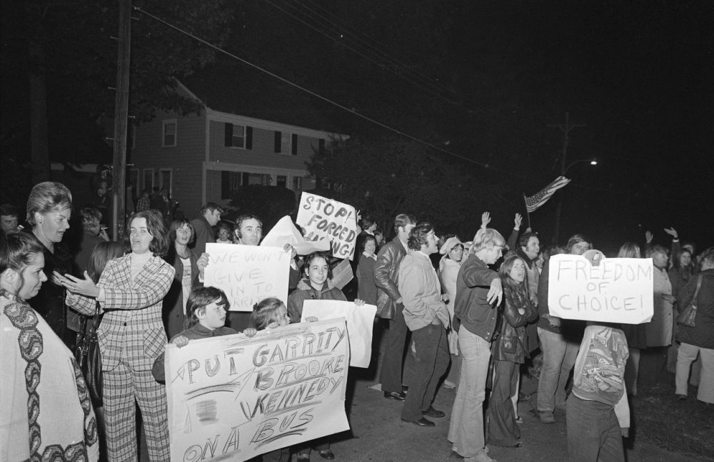 Demonstrators carrying signs gather the night of Oct. 5, 1974 outside the home of U.S. District Judge W. Arthur Garrity protesting the forced busing of Boston's schoolchildren.
