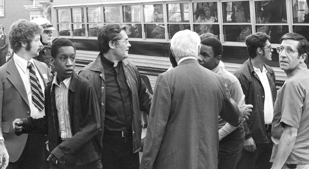 Two African American students walk through line of officials as they left bus to attend the predominantly white South Boston High in South Boston on Thursday, Sept. 12, 1974. It was the first day of a court-ordered busing program to integrate Boston public schools. (AP)