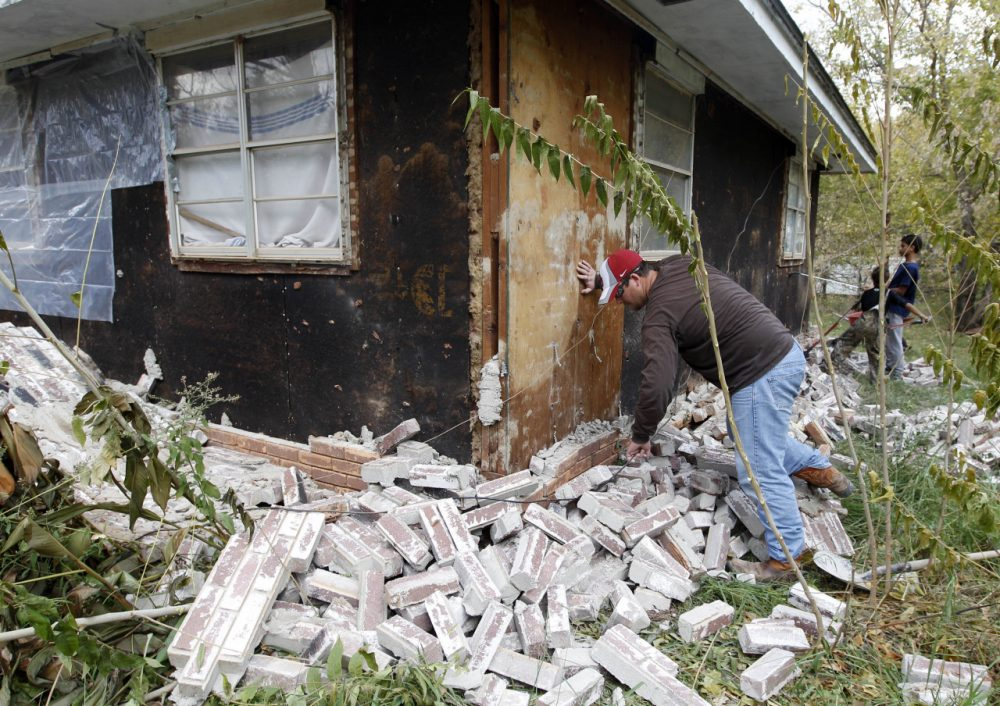 Chad Devereaux examines bricks that fell from three sides of his in-laws home in Sparks, Okla., Nov, 6, 2011, following two earthquakes that hit the area in less than 24 hours. (Sue Ogrocki/AP)