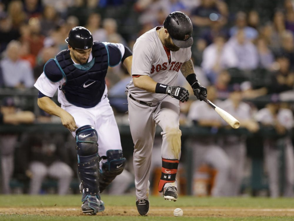 Mike Napoli steps over the ball as Mariners catcher Mike Zunino gives chase in the ninth inning of Tuesday's game in Seattle. Zunino made the play for the out. The Mariners won 8-2. (Elaine Thompson/AP)