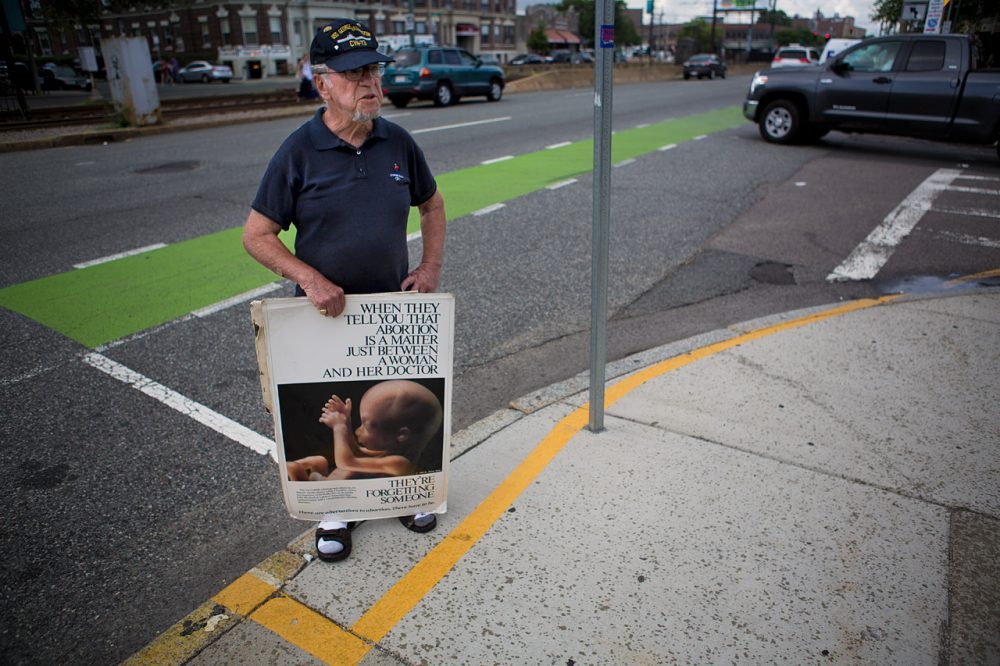 A protester stands outside the 35-foot buffer zone at a Planned Parenthood facility on Commonwealth Avenue in Boston on Thursday, after the Supreme Court struck down the state's buffer zone law. (Jesse Costa/WBUR)