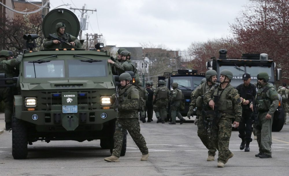 A SWAT team unloads from their armored vehicles as they go door to door while searching for a suspect in the Boston Marathon bombings in Watertown, Mass., Friday, April 19, 2013. (AP)