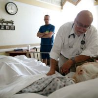 In this 2009 file photo, Dr. Joel Policzer checks on Lillian Landry in the hospice wing of an Oakland Park, Fla. hospital. Unlike most of Policzer's patients she made end-of-life decisions. (AP File)