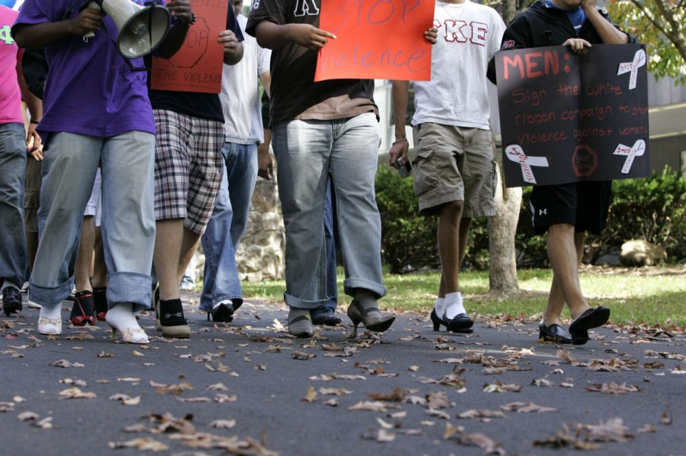 Male students at Ramapo College walk in women's shoes for a march against violence against women in 2008.  (Mike Derer/AP)