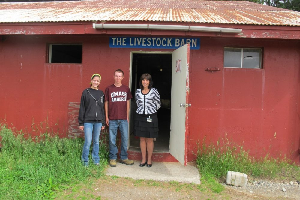 Aggie seniors Jenna Illingworth and Austin Broderick stand with Aggie Principal Tammy Quinn in front of the livestock barn in Walpole, Mass. (Anthony Brooks/WBUR)