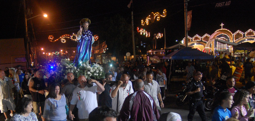 Men carry the St. Peter statue past the Fiesta's carnival and altar during the closing procession Sunday night. (Greg Cook)