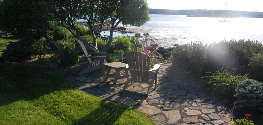 In this garden off Eastern Point Road in East Gloucester, the expansive lawn ends in patios situated under dwarf apple trees along the water's edge. (Greg Cook)