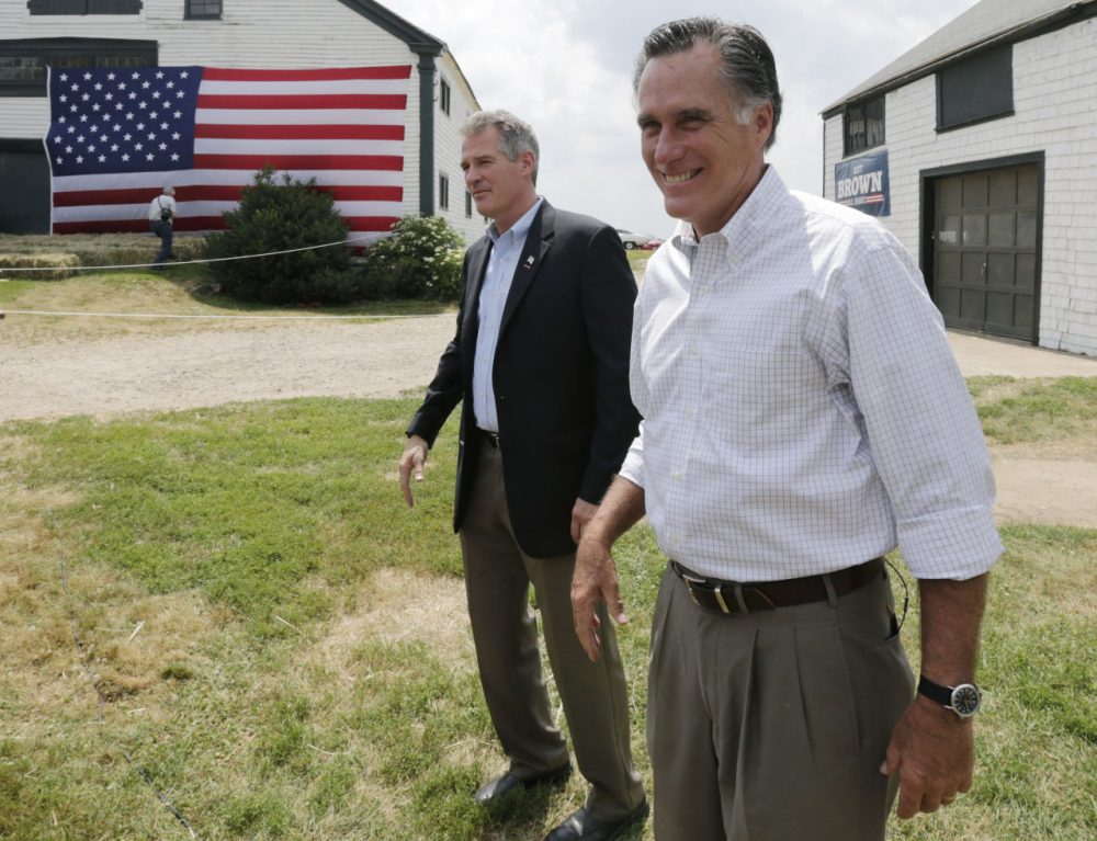 Mitt Romney, the former Republican presidential nominee, stands with New Hampshire Senate candidate Scott Brown, left, as they wait to be introduced during a campaign stop at a farm in Stratham, N.H., Wednesday, July 2, 2014.  Brown, who is facing incumbent Democrat U.S. Sen. Jeanne Shaheen, was endorsed by Romney at the event.  (Charles Krupa/AP)