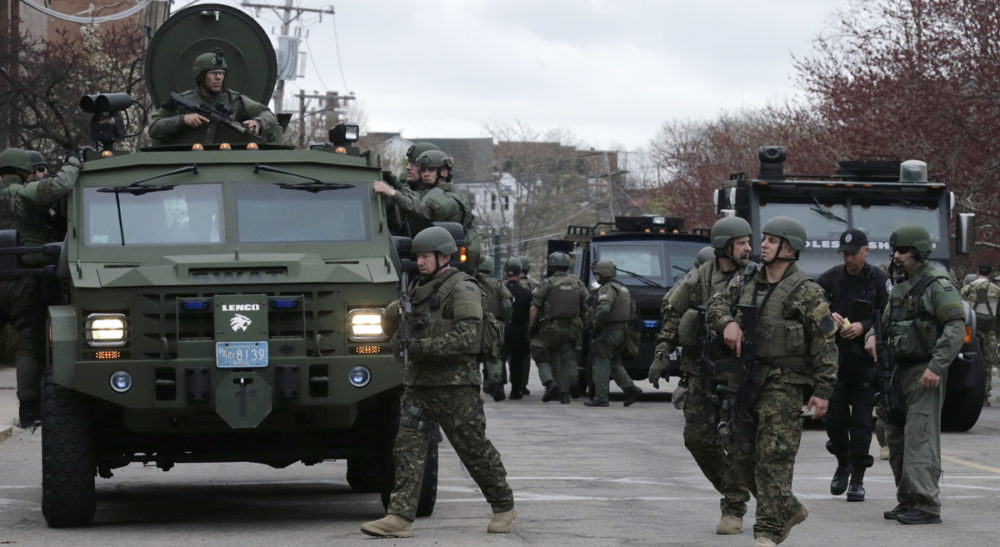 "Carol Rose and Kade Crockford: ""A thick blue wall of police silence is obstructing the public's access to timely and accurate data about SWAT deployments."" Pictured: A SWAT team unloads from their armored vehicles as they go door to door while searching for a suspect in the Boston Marathon bombings in Watertown, Mass., Friday, April 19, 2013. (Charles Krupa/AP)"