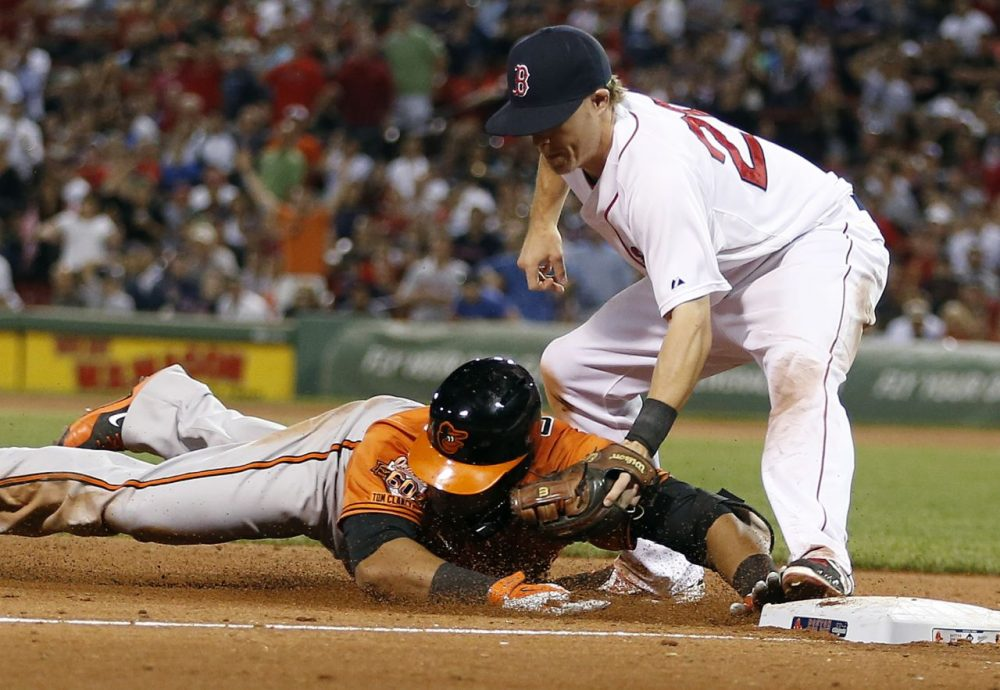 Boston Red Sox's third baseman Brock Holt, top, tags Baltimore Orioles' Nelson Cruz trying to reach on a double in the eighth inning of the second game of a baseball doubleheader in Boston, Saturday, July 5, 2014. (Michael Dwyer/AP)