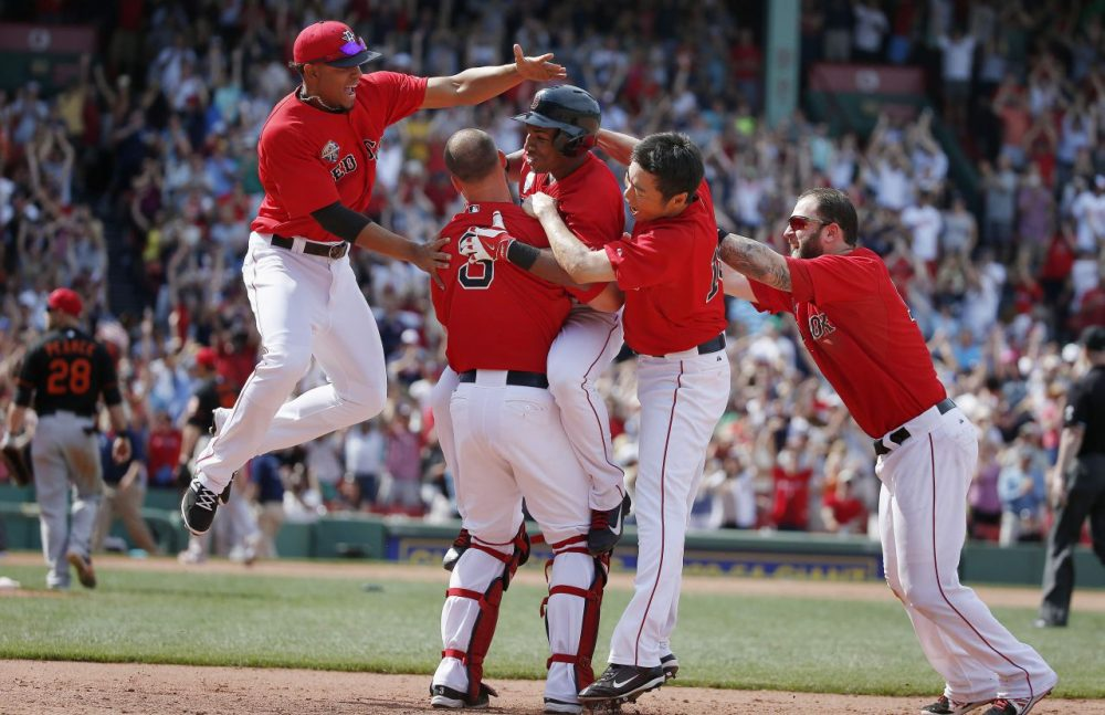Boston Red Sox's Jonathan Herrera, center, celebrates his game-winning RBI single with teammates Xander Bogaerts, left, David Ross (3), Koji Uehara, second from right, and Mike Napoli, right, in the ninth inning of the first game of a baseball doubleheader against the Baltimore Orioles in Boston. (Michael Dwyer/AP)