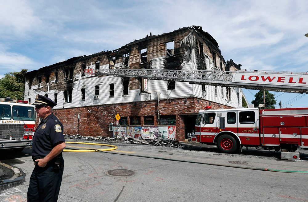 A policeman secures the scene of a burned three-story apartment and business building in Lowell, where seven people died in a fast-moving fire. (Elise Amendola/AP)