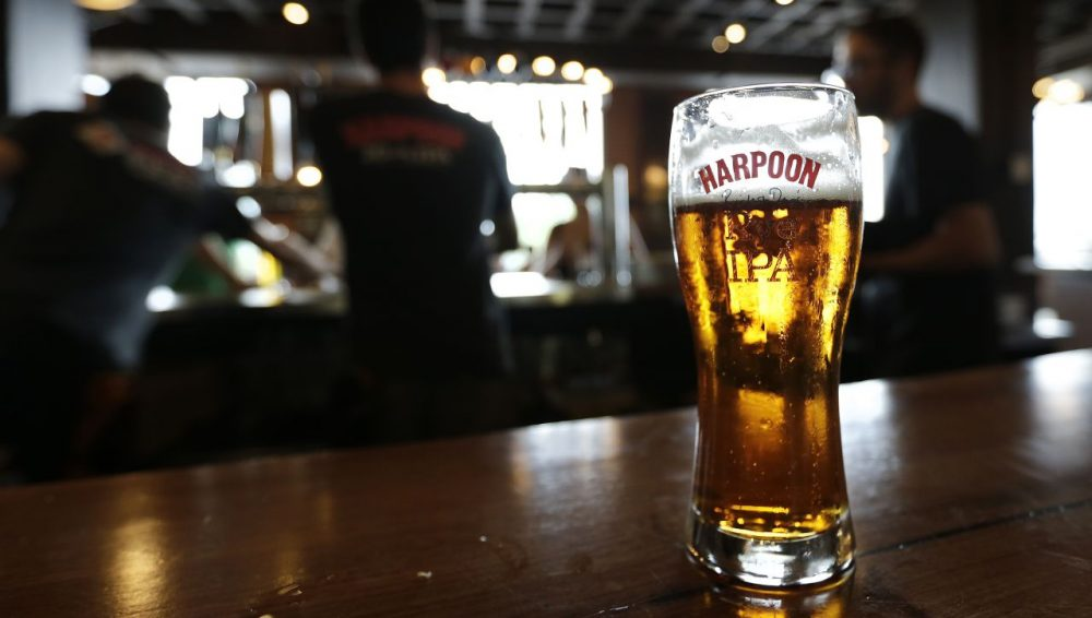 In this July 1, 2013 photo a glass of Rich and Dan's Rye IPA rests on the counter as bartenders pour drafts for patrons in the Beer Hall at the Harpoon Brewery in the Seaport District of Boston. (Charles Krupa/AP)