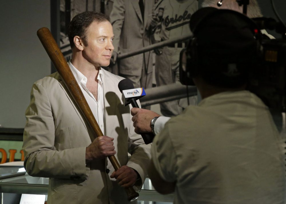 Goldin Auctions president Ken Goldin holds a baseball bat that Babe Ruth used early in his career, Wednesday, July 9, 2014, in Baltimore, as he is interviewed during a media preview of sports memorabilia slated for auction to mark the 100th anniversary of Ruth's major league debut. The auction is scheduled to take place July 12, the day after the anniversary, and the organizers estimate that 125 items to be auctioned off could fetch as much as $10 million. (Patrick Semansky/AP)