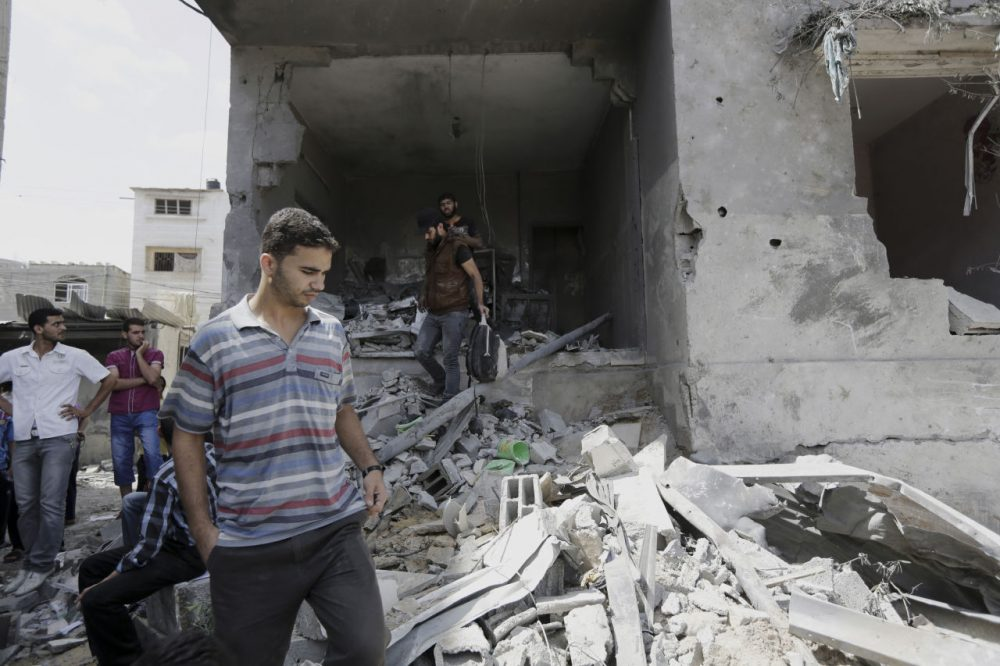 Palestinians look at the damaged house of Gaza's police chief Taysir al-Batsh after it was hit by an Israeli missile strike in Gaza City, Sunday, July 13, 2014. The strike that hit the home and damaged a nearby mosque as evening prayers ended Saturday, killed at least 18 people, wounded 50 and left some people believed to be trapped under the rubble, said Palestinian Health Ministry official Ashraf al-Kidra. (Adel Hana/AP)