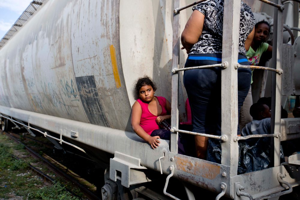 A young migrant girl waits for a freight train to depart on her way to the U.S. border in Ixtepec, Mexico, on July 12. (Eduardo Verdugo/AP)