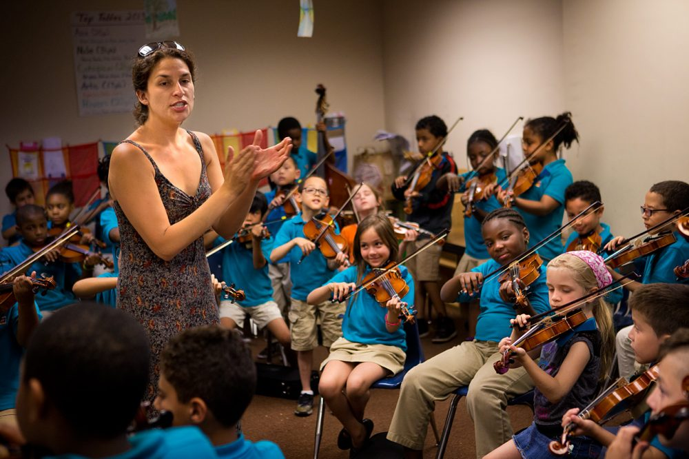 Kathleen Jara, co-director of the El Sistema program at the Conservatory Lab Charter School in Boston, directs orchestra students during a rehearsal. (Jesse Costa/WBUR)