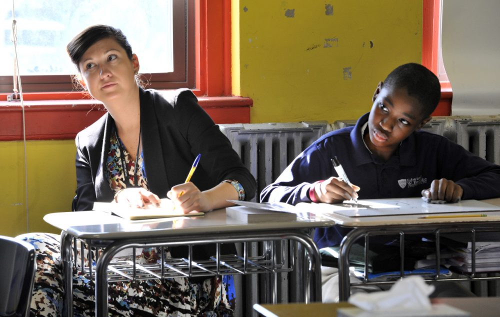 Tracy Taylor, assistant head teacher with Kingsford Community School of London watches a sixth grade math lesson beside student Dema'd McCray, 12, at the Brooke Roslindale Charter School in Boston. (Josh Reynolds/AP)