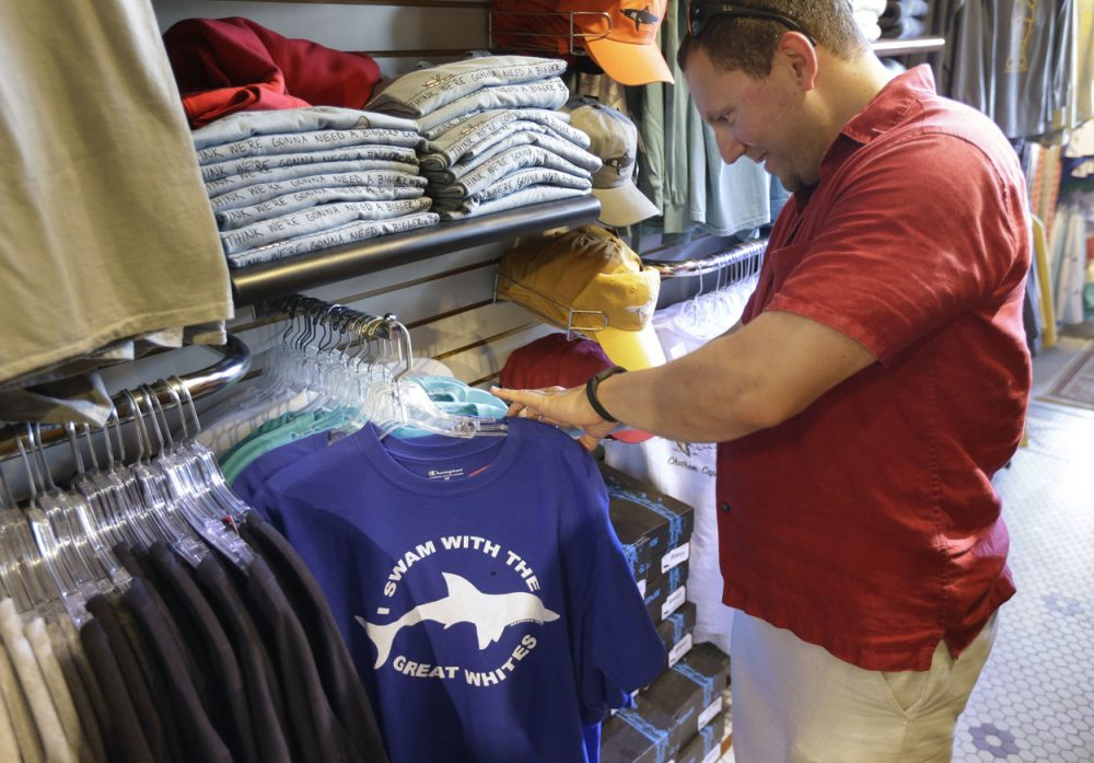 Vacationer Mark McCurdy, of Everett, examines shark-themed clothing at the Chatham Clothing Bar in Chatham, Mass. Growing sightings of great white sharks off Cape Cod are generating business for local entrepreneurs as residents and tourists seek a glimpse of the offshore predators -- or purchase their shark-themed memorabilia and apparel. (Steven Senne/AP)