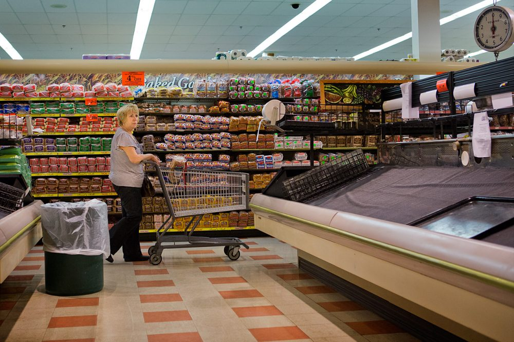 A customer walks past empty shelves at a Somerville Market Basket on July 22. The 40-day dispute is now over. (Jesse Costa/WBUR)