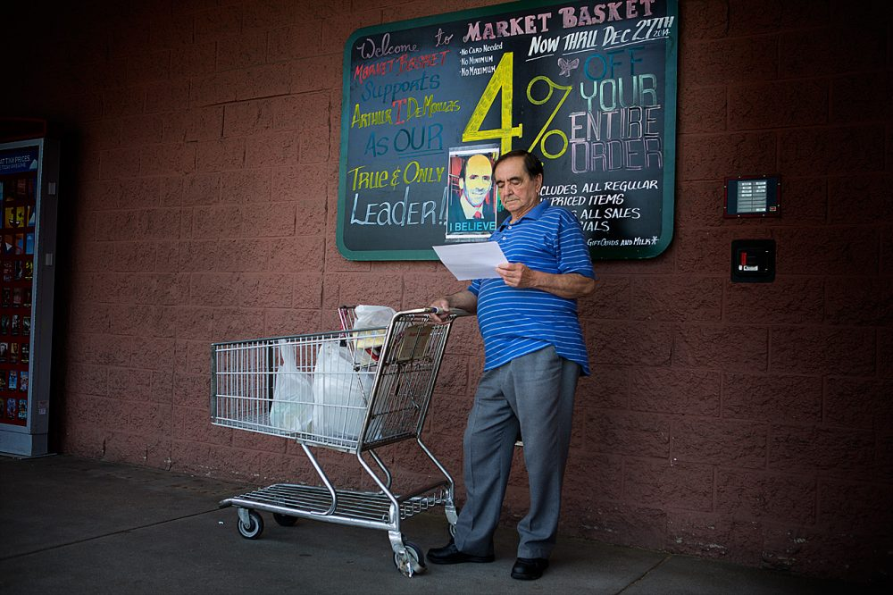 A shopper at the Somerville Market Basket reads a sheet of paper calling for people not to shop at the Market Basket store until Arthur T. Demoulas is reinstated as CEO. (Jesse Costa/WBUR)