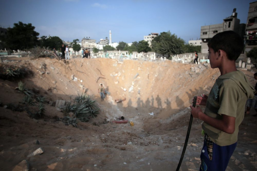 Palestinians check a crater caused by an Israeli strike at a cemetery in the Jabaliya refugee camp, northern Gaza Strip, on Monday. (Khalil Hamra/AP)