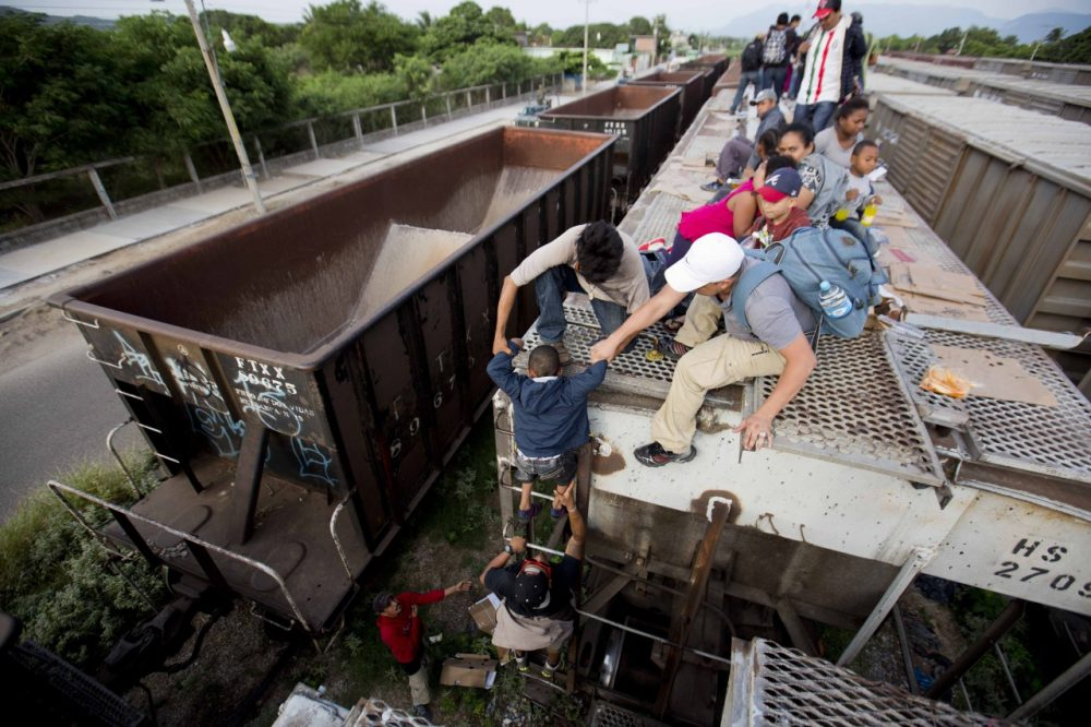 A young boy is is helped down from the top of a freight car, as Central Americans board a northbound freight train in Ixtepec, Mexico. (Eduardo Verdugo/AP)