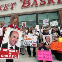 """Thomas Kochan: """"Unless there is a change of course... all parties -- owners, employees and customers -- will lose.""""  Pictured: Market Basket assistant managers Mike Forsyth, left, and John Surprenant, second from left, hold signs while posing with employees in Haverhill, Mass., Thursday, July 24, 2014, in a show of support for Arthur T. Demoulas. The former chief executive of the Market Basket supermarket chain whose ouster has led to employee protests, customer boycotts and empty shelves, says he wants to buy the entire company. (AP)"""