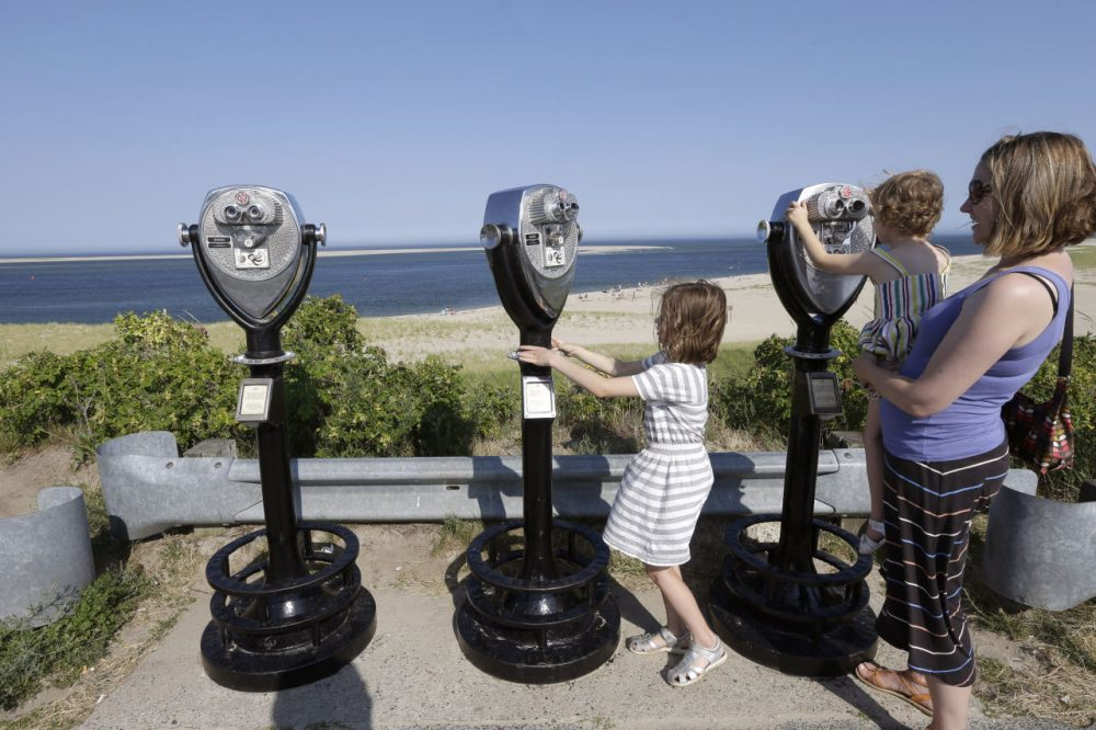 In this July 2, 2014 photo, Molly Saint-James, of Baltimore, right, helps her daughters Ellie McDonald, left, 6, and Poppy McDonald, 3, use telescopic viewers overlooking a beach while on vacation in Chatham, Mass. Growing sightings of great white sharks off Cape Cod are generating business for local entrepreneurs as residents and tourists seek get a glimpse of the offshore predators -- and purchase their shark-themed memorabilia. (Steven Senne/AP)