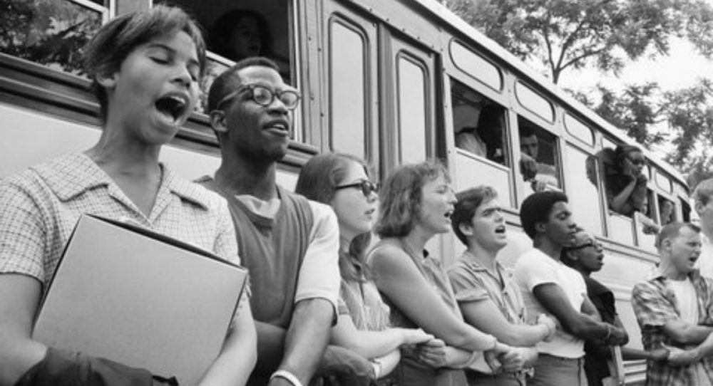 """J. Kates: """"Fifty years later, the significance of 'Freedom Summer,' the Mississippi Voting Project of 1964, gets measured not by our accomplishments, but by our losses."""" Pictured: The author, fifth from left, and fellow volunteers sing beside their bus in Oxford, Ohio, in June 1964 before leaving for Mississippi to help blacks register to vote. (Ted Polumbaum/Newseum collection. Used by permission)"""