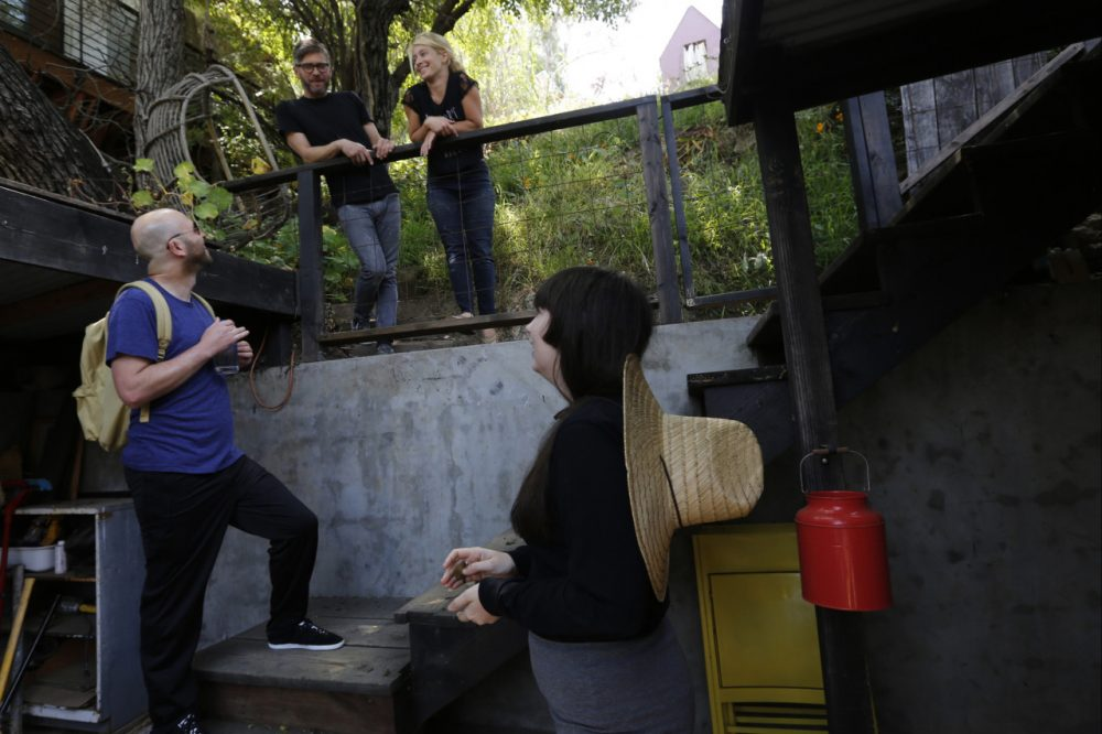 In this Monday, May 19, 2014 photo, ceramist and Airbnb host Jonathan Entler, top left, and his daughter Ruby, top right, talk to guests, James Green, bottom left, and Camille Smithwick from Manchester, U.K., at their Echo Park home in Los Angeles. (AP)