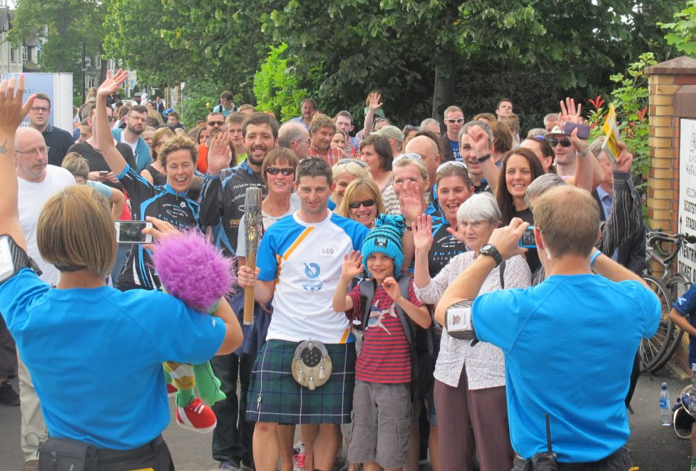 A member of the Queen's Baton Relay in the Scotstoun section of Glasgow, Scotland poses for photographs before beginning his (short) portion of the 190,000 km relay. The baton is en route to the Commonwealth Games Opening Ceremony. (Doug Tribou/Only A Game)