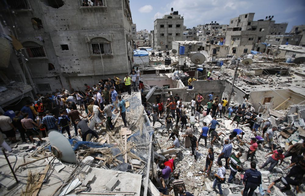 Palestinians look for survivors under the rubble of the al-Bakri family home destroyed by an Israeli strike in Gaza City Monday. (Hatem Moussa/AP)
