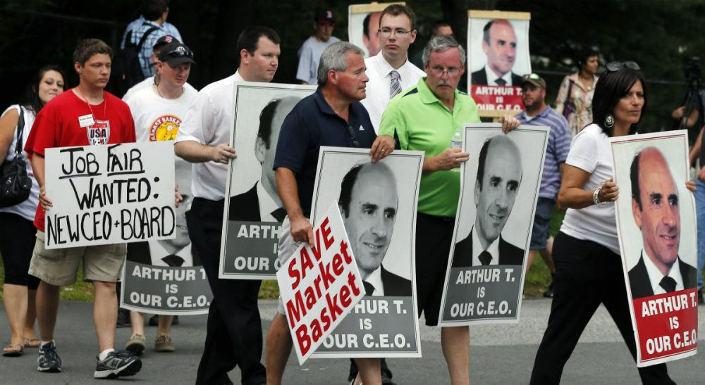 "The MIT Sloan School of Management professor says the stakes are too high, and there is too much for all involved to lose, to let the conflict escalate further. Pictured: Protesters holding ""Arthur T"" signs taunt an occupant of a car driving from a Market Basket Supermarket job fair in Andover, Mass., Monday, Aug. 4, 2014. (Elise Amendola/AP)"