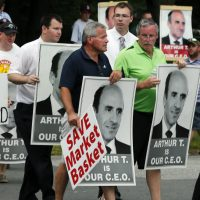 """The MIT Sloan School of Management professor says the stakes are too high, and there is too much for all involved to lose, to let the conflict escalate further. Pictured: Protesters holding """"Arthur T"""" signs taunt an occupant of a car driving from a Market Basket Supermarket job fair in Andover, Mass., Monday, Aug. 4, 2014. (Elise Amendola/AP)"""