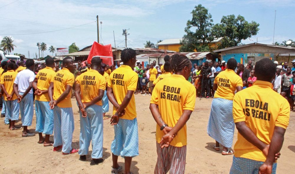 People working for a petroleum company take part in an Ebola awareness campaign in Liberia on Monday. (Abbas Dulleh/AP)