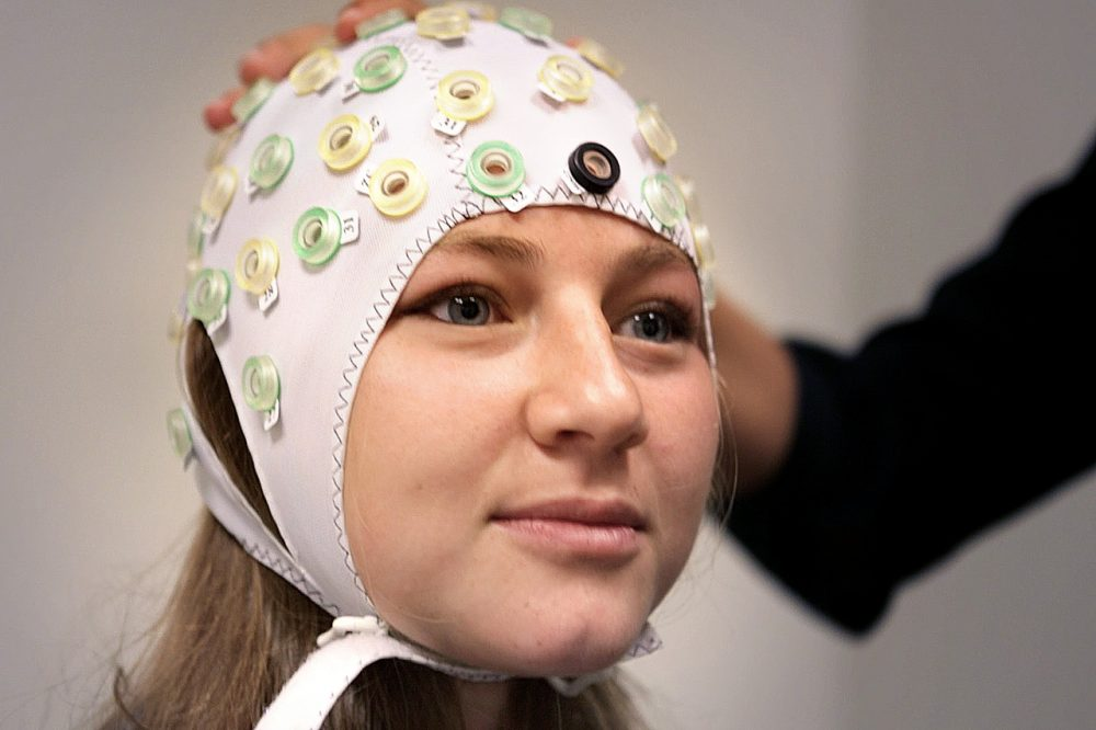 Sarah Beth Spitzer, a research assistant at Harvard University, wears an EEG cap, used to localize the regions of the brain needed to stimulate during the test. (Jesse Costa/WBUR)