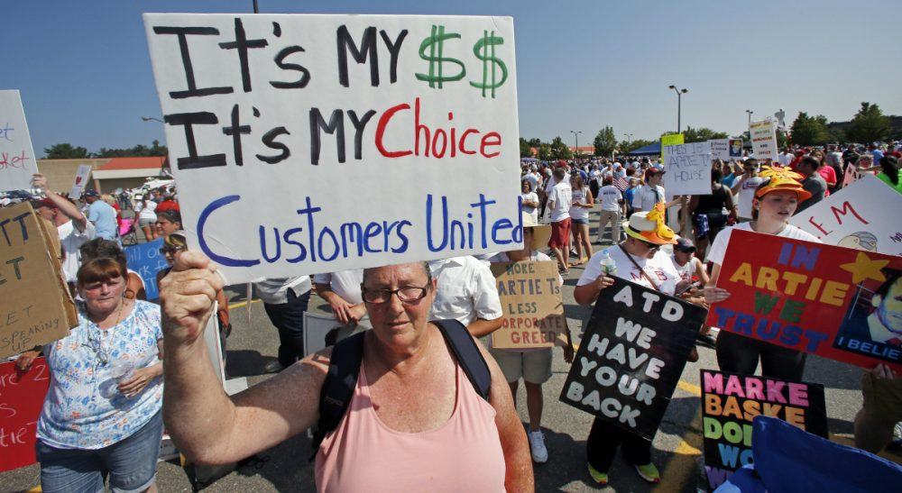 Why community, state and regional leaders have an enormous stake in resolving the Market Basket fiasco. Pictured: Protesters hold signs during a rally at Market Basket in Tewksbury, Mass., Tuesday, Aug. 5, 2014. Thousands of Market Basket supermarket employees and their supporters are calling for the reinstatement of their fired CEO, even as the company began a three-day job fair to replace employees who have refused to work during a revolt that is costing the supermarket chain millions. (Elise Amendola/AP)