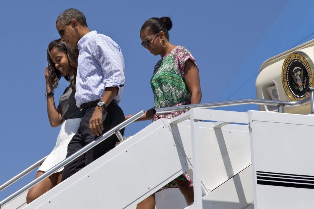 President Barack Obama walks with daughter Malia Obama and first lady Michelle Obama as they exit Air Force One at Cape Cod Coast Guard Air Station Saturday en route to Martha's Vineyard. (Jacquelyn Martin/AP)