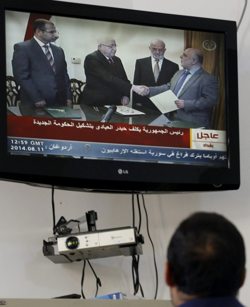 A journalist watches as Iraqi President Fuad Masum shakes hands with deputy parliamentary speaker Haidar al-Abadi, who has been tasked with forming a government, during a brief ceremony broadcast on state television on August 11, 2014, in Baghdad. (Sabah Arar/AFP/Getty Images)