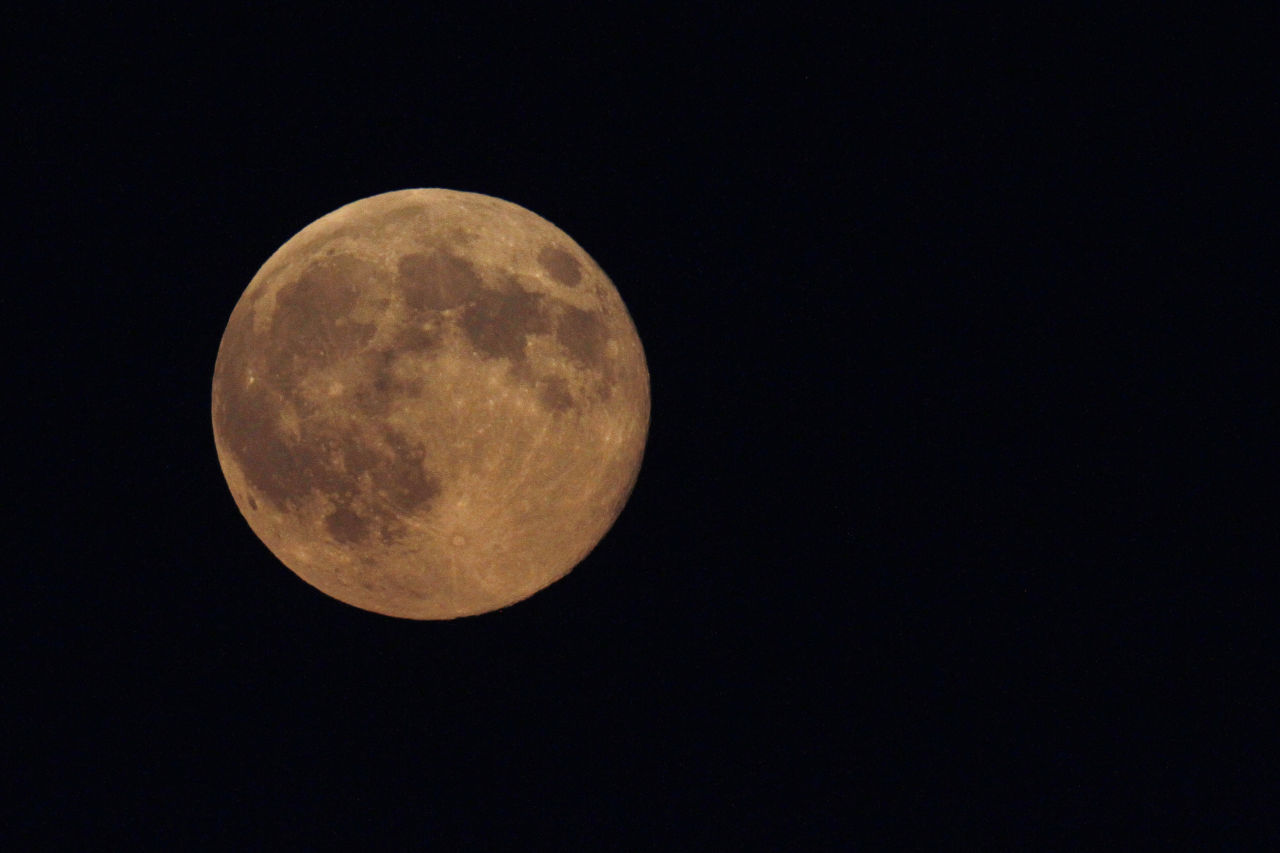 The supermoon appears yellow as the sky darkens over Edgartown, Mass., Sunday, Aug. 10, 2014, on the island of Martha's Vineyard. President Barack Obama and his family are vacationing on the island. (Jacquelyn Martin/AP)