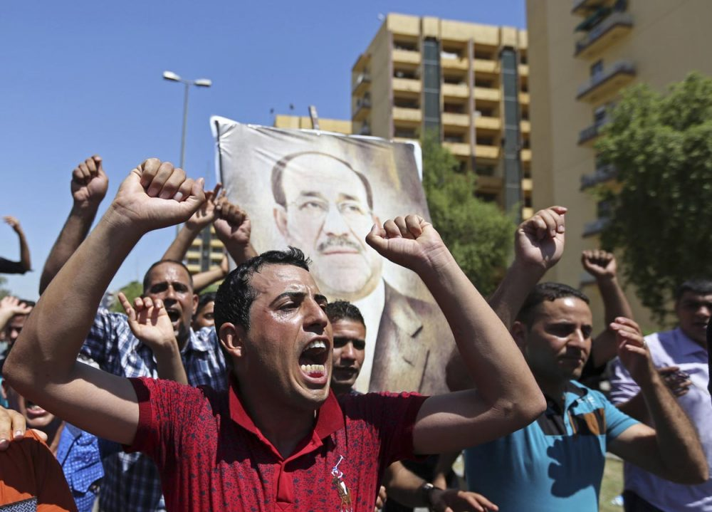 Iraqis chant pro-government slogans and display placards bearing a picture of embattled Prime Minister Nouri al-Maliki during a demonstration in Baghdad on Monday (Hadi Mizban/AP)