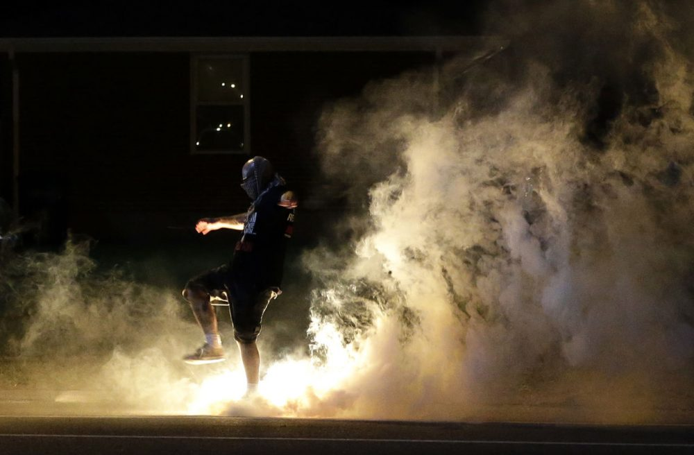 A protester kicks a smoke grenade that had been deployed by police back in the direction of police on Wednesday in Ferguson, Mo. in the suburb that has been rocked by racial unrest. (Jeff Roberson/AP)
